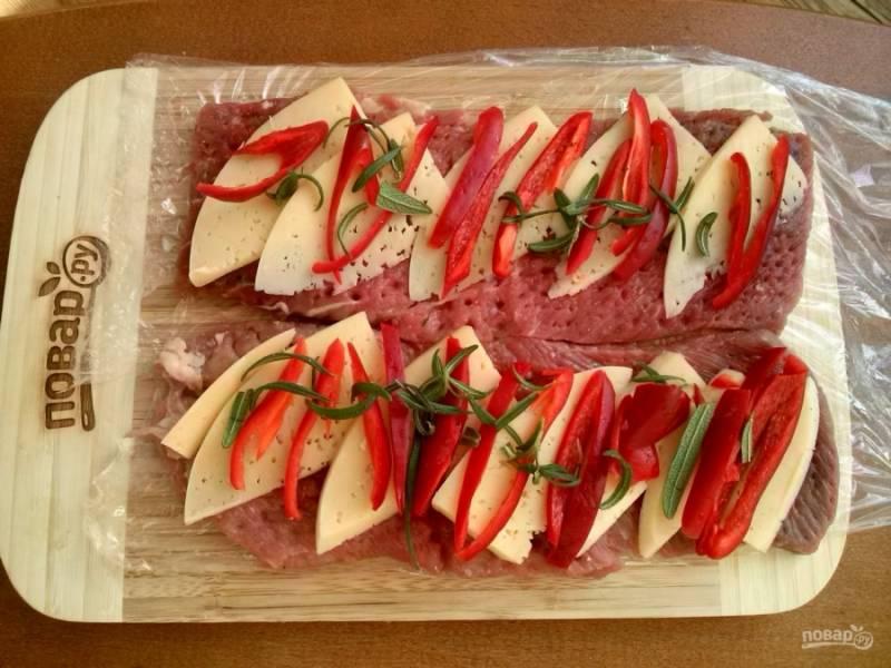 Выложите начинку поверх мясных пластов, сверните рулеты и закрепите их силиконовыми завязками или кулинарной нитью.