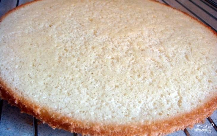 Яйца разбиваем в глубокую миску и взбиваем их до образования густой пены. Добавляем 4 ложки сахара и продолжаем взбивать, пока сахар полностью не растворится. Теперь всыпаем просеянную муку и аккуратно лопаткой вмешиваем ее складывающими движениями. Форму для запекания диаметром 23-24 см накрываем пергаментом и выкладываем в нее приготовленную смесь, выравниваем. Ставим в разогретую до 180 градусов духовку и выпекаем 15 минут. Затем достаем бисквит и ждем, пока он полностью остынет.