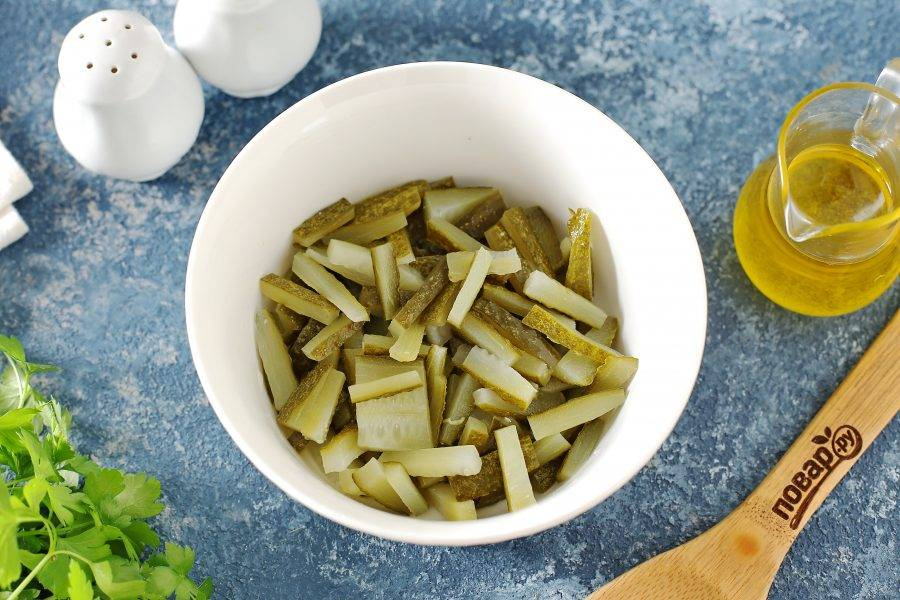 Огурцы нарежьте небольшой соломкой, слегка отожмите и переложите в салатник.