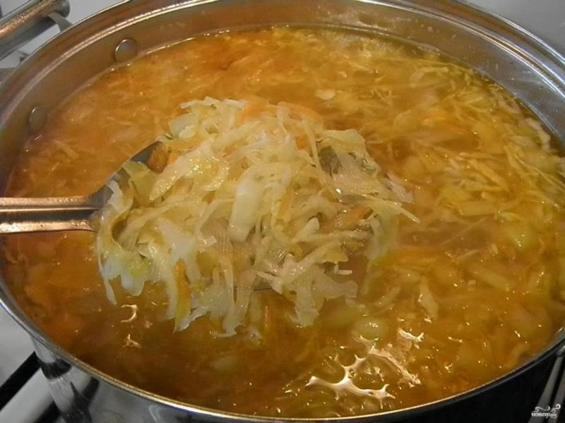 Добавьте в суп жареную капусту и овощи, перемешайте, откорректируйте на соль и проварите пару минут. В конце варки добавьте зелень.