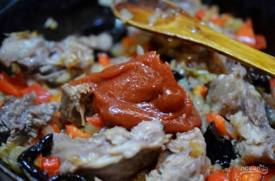 Поочередно добавьте в сковороду с мясом и луком нарезанные перец, чернослив и томатную пасту. Обжаривайте минут 5.