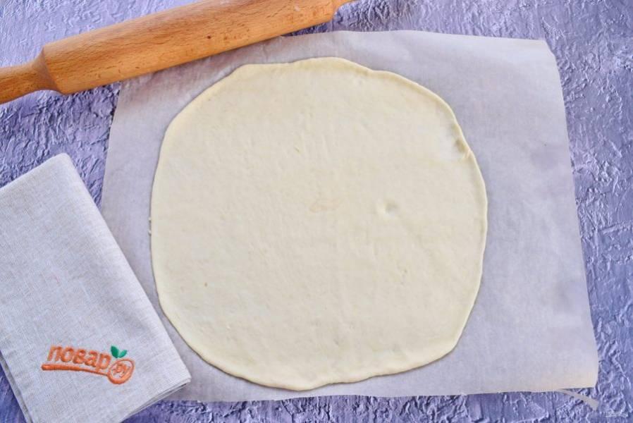 6.    Обомните тесто, разделите его на 2 части. Одну часть раскатайте в тонкую круглую лепешку. Поместите лепешку на пергамент для выпечки или противень, смазанный маслом.