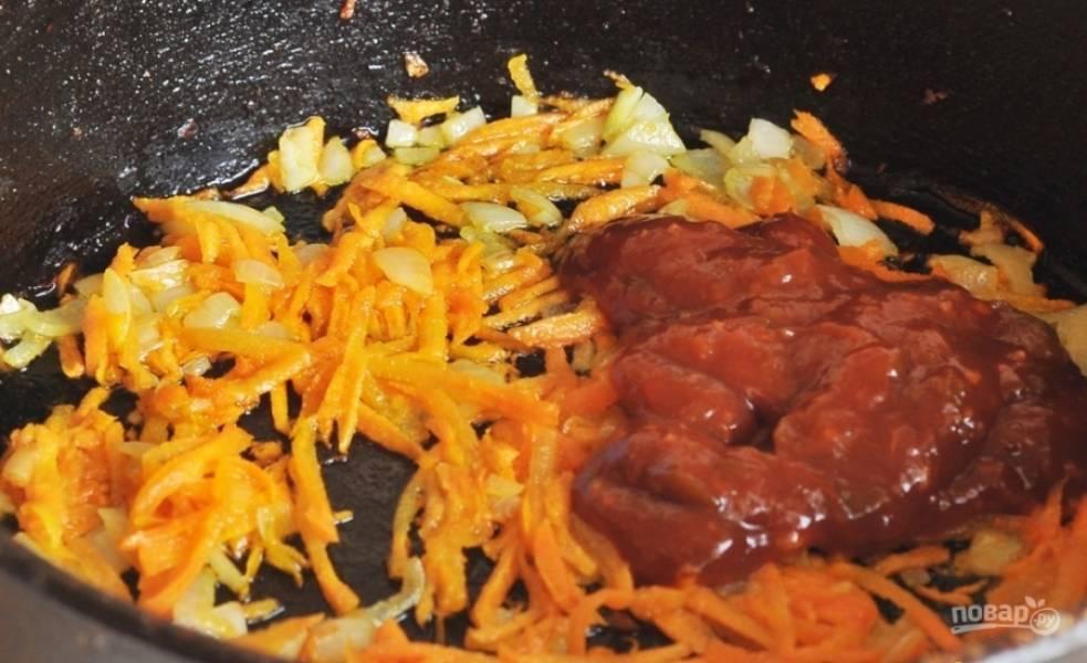 Обжарьте до готовности в масле морковь и лук. В конце добавьте к ним кетчуп. Заправку внесите в суп за 3 минуты до полной готовности.