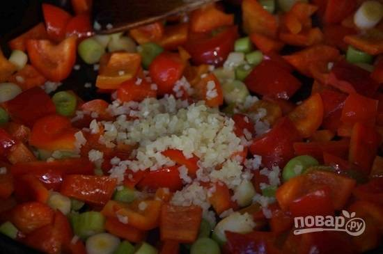 Разогреем сковороду с маслом. Перцы очистим и нарежем кубиками среднего размера. Нарежем лук. Выложим овощи на сковороду и обжариваем минуту. Добавим измельченный чеснок, перемешаем.