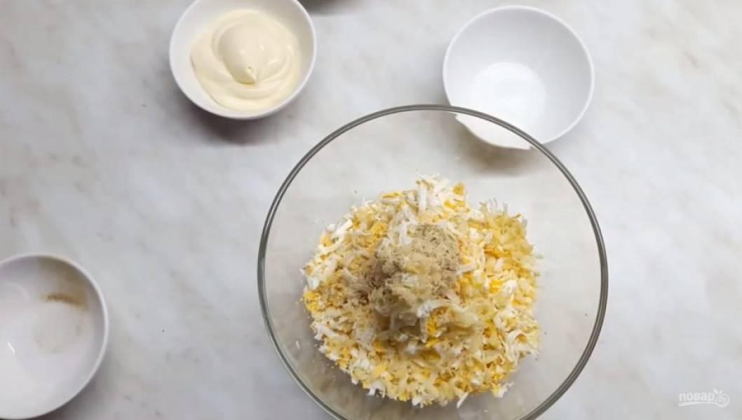 1. Поставьте запекаться морковь в духовке в фольге (при 200 градусах до мягкости). На мелкой терке натрите твердый и плавленый сыр. Натрите два отварных яйца и чеснок. Добавьте белый перец, соль и майонез (можете добавить магазинный или приготовить домашний).