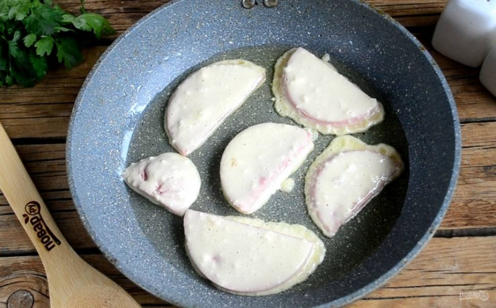 Сначала обмакните каждый кусочек колбасы в кляр, а затем выложите на сковороду с разогретым растительным маслом.