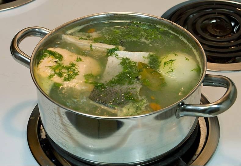 В приготовленный бульон кладем порционные куски рыбы, обжаренную морковь и доводим до кипения, снимаем образовавшуюся пену и уменьшаем огонь до минимума, добавляем соль по вкусу, на медленном огне продолжаем варить еще 10‒20 минут в зависимости от величины кусков рыбы.   Кастрюлю крышкой не накрывать. И часто уху мешать не стоит, чтобы куски рыбы не развалились, если нам нужна уха, а не каша.  За пару минут до готовности добавляем 15 г сливочного масла для придания жирности ухе. Готовую уху посыпать свежей зеленью и дать ей настояться еще 20 минут.