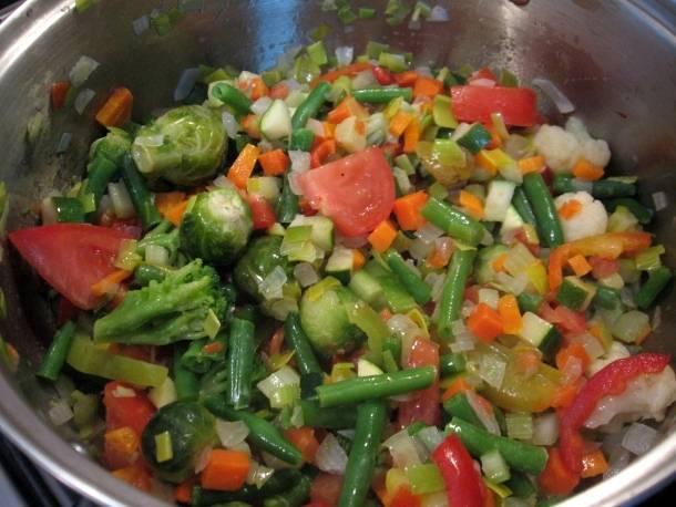 После вина добавляем замороженные овощи, перемешиваем все и доводим до кипения.