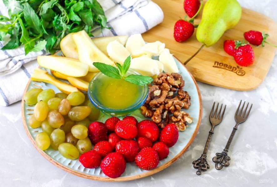 Выложите в пиалу или креманку мед, поместите емкость в центр тарелки. По бокам выложите промытые ягоды клубники и винограда, разрезанные на четыре части шарики моцареллы (если они мелкие, то их разрезать не нужно), ядра грецких орехов и ломтики груш. Сразу же подайте закуску для портвейна к столу, сохраняя в ягодах все витамины.