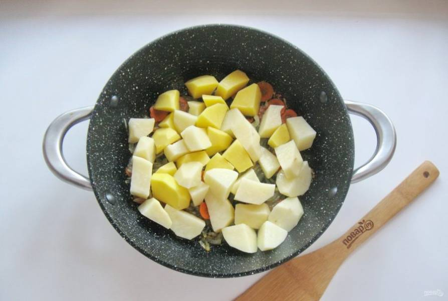 Картофель очистите, помойте и нарежьте кубиками. Добавьте к овощам в сковороду.