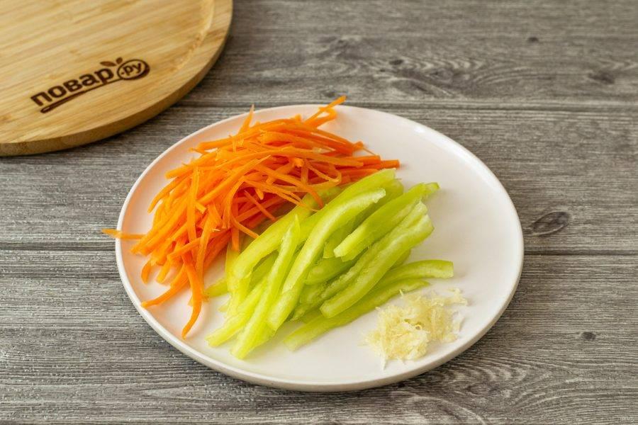 Морковь помойте, очистите и натрите на терке для моркови по-корейски. У болгарского перца удалите хвостик и семена, нарежьте соломкой. Чеснок пропустите через пресс.