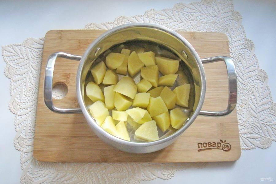 Картофель очистите, помойте и нарежьте произвольно. Выложите в кастрюлю.