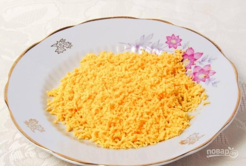В это же время яйца отварите вкрутую. Желтки отделите от белков. Натрите их на мелкой тёрке.