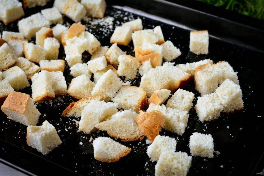 Разложите хлебные кубики на противне и отправьте запекаться в духовку при температуре 200 градусов на 10-12 минут.