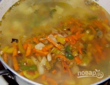 Следом за кукурузой отправляем в кастрюлю обжаренные овощи. После закипания добавим соль и перец.