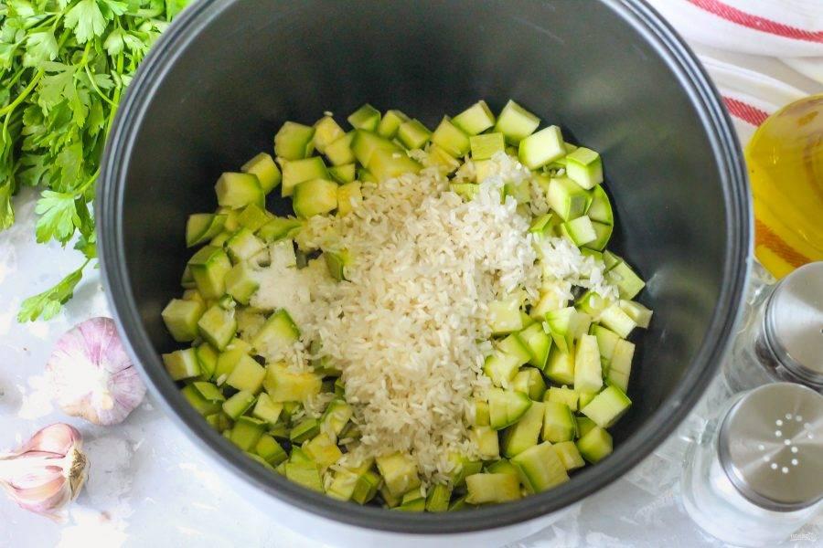 Смажьте чашу мультиварки растительным маслом. Высыпьте в нее кабачковую нарезку и промытый рис. Добавьте соль.