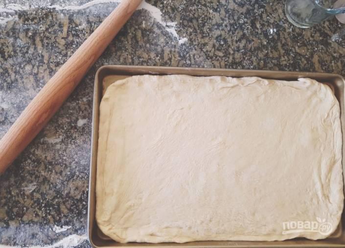 Тесто для пиццы растяните по форме противня, присыпав его мукой.