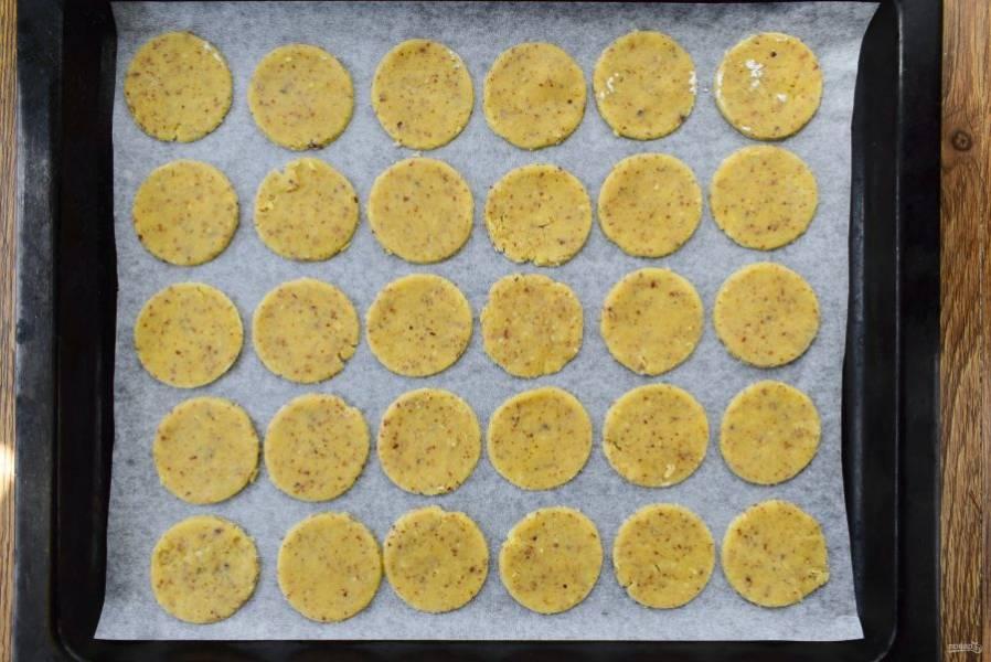 Раскатайте тесто в пласт толщиной 3-4 мм. Вырубите кружки по 5-8 см в диаметре. Разложите заготовки на противне с пергаментом или силиконовым ковриком для выпечки.