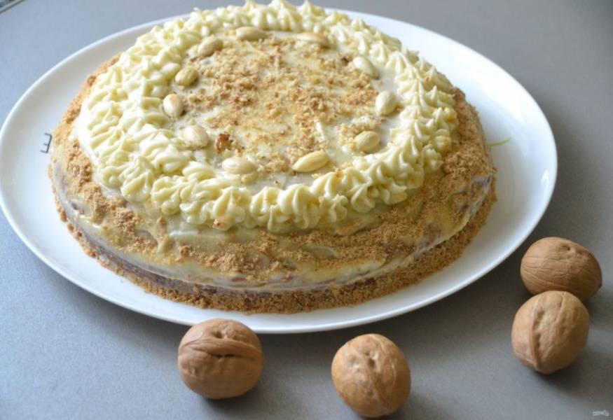 Уложите верхний корж, смажьте верх и бока  торта кремом, примерно 1/3 крема переложите в кондитерский мешок и украсьте торт сверху, можно присыпать остатками орехов. Бока можно обсыпать крошкой от печенья.