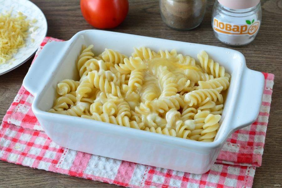 Выложите макароны в форму для запекания. Залейте яично-молочным соусом.
