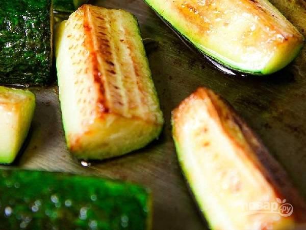3. Разогрейте растительное масло, выложите зубчик чеснока целиком, предварительно чуть раздавив его, чтобы он лучше отдавал аромат. Как только он поджарится, аккуратно достаньте. Выложите на сковороду цуккини и жарьте на среднем огне. В процессе посолите и поперчите по вкусу, добавьте чеснок и ложку тертого сыра.