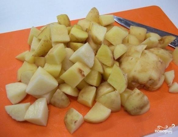 3. В отдельной кастрюльке поставьте вариться яйца вкрутую. Параллельно очистите и нарежьте небольшими кубиками картофель.
