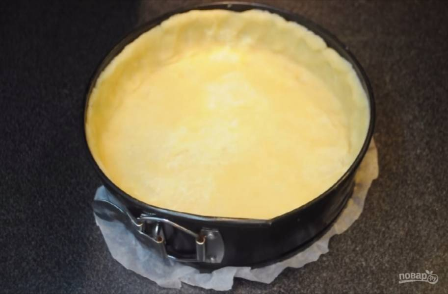 3. Сначала руками, а потом скалкой раскатайте тесто в корж толщиной в полсантиметра. Форму, застеленную пергаментной бумагой, смажьте маслом и равномерно распределите в ней корж, сформировав при этом края. С помощью вилки сделайте проколы в тесте, чтобы оно не вздулось. Выпекайте в разогретой до 180 градусов духовке 20 минут.