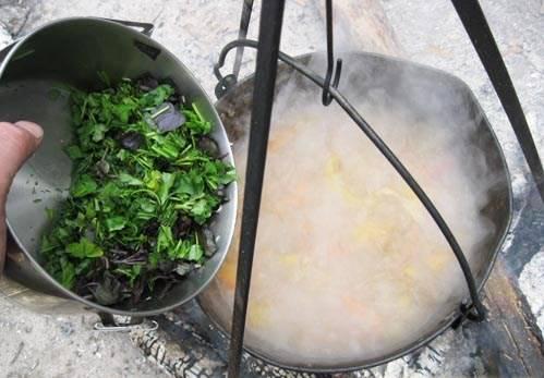 Через 10 минут после картофеля кладем в шурпу половину нарезанной зелени: базилика, петрушки, кинзы и укропа.