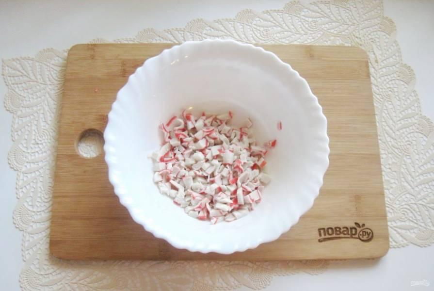 Крабовые палочки или крабовое мясо мелко нарежьте и выложите в салатник.
