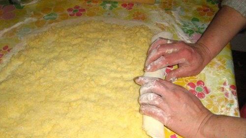 2. Тесто раскатаем в большой прямоугольник толщиной 0.5 см, посыпем начинкой. Аккуратно сворачивает тесто с начинкой в плотный рулет.