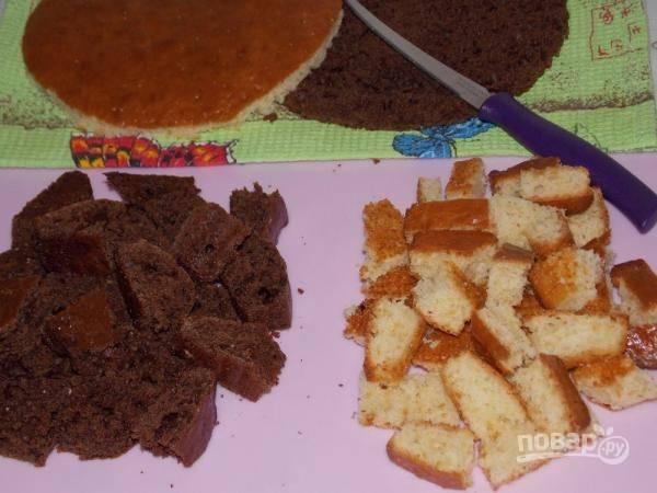 Остужаем бисквиты, обрезаем около 1/4 коржей по краям, формируя круг или квадрат. Обрезки режем примерно одинаковыми кубиками.