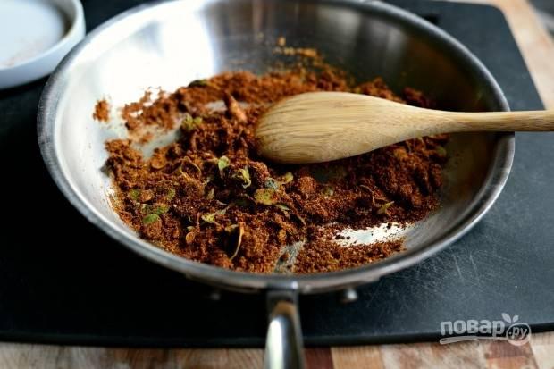 7. А следом всыпьте чили, кайнеский и чёрный перец, тмин. Помешивая, готовьте специи буквально 1 минуту.