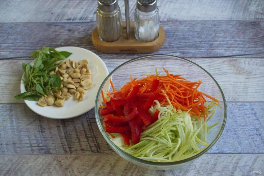 Перец нарежьте тонкой соломкой, кабачок и морковь натрите на терке для корейской морковки. Базилик измельчите. Добавьте арахис. Посолите и перемешайте.