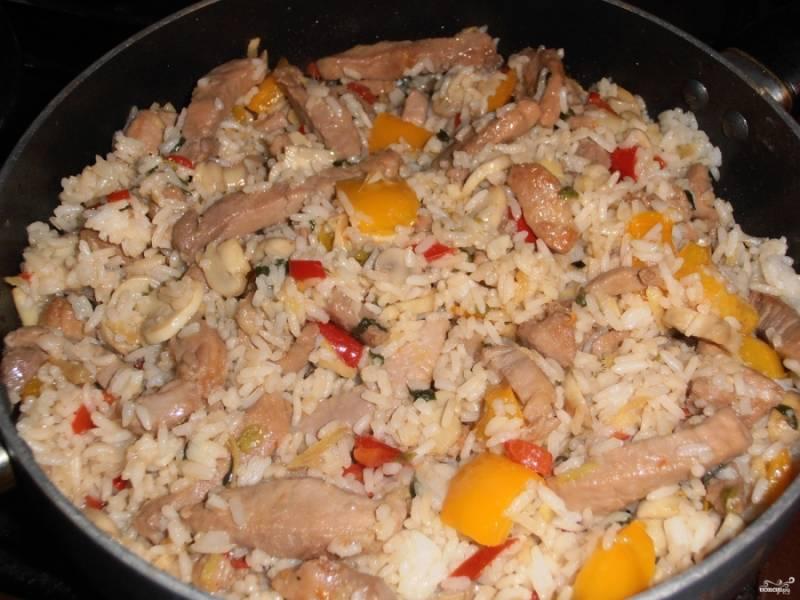 Потом к овощам на сковороду верните курицу и рис отварной. Перемешайте все, посолите и поперчите, добавьте приправ по вкусу. Готовьте минуту или две.