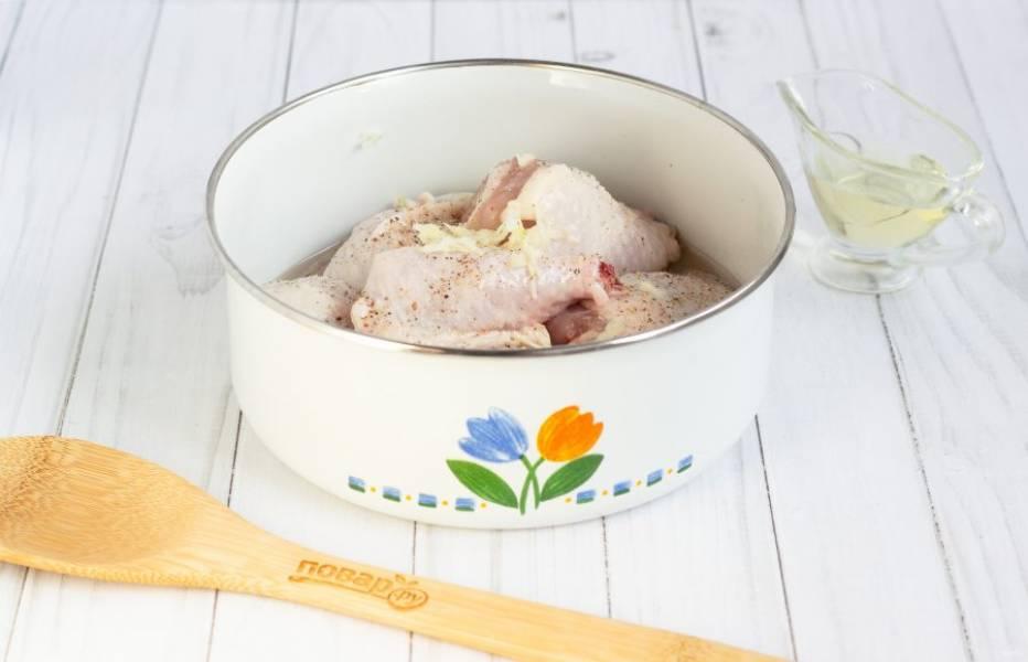Куриные части помойте, обсушите бумажным полотенцем, посолите и поперчите по вкусу. Добавьте любимые специи для курицы. Также добавьте натертый на мелкой терке чеснок и 1 ст. л. растительного масла. Тщательно всё перемешайте.