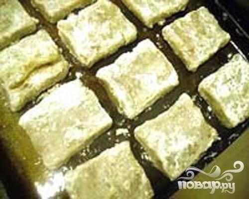 3.Растительным маслом смазываем противень. В муке хорошо обваливаем каждый кусочек рыбы и  выкладываем на противень.