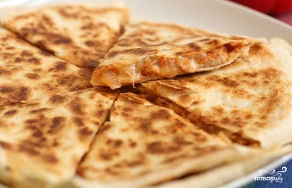 5.Поджарьте с одной стороны, переверните, подрумяньте с другого бока. Приготовьте следующую кесадилью со свининой. Положите на тарелку. Разделите на сегменты. Вкуснее будет, если вы подадите блюдо горячим, с пылу с жару. Приятного аппетита.
