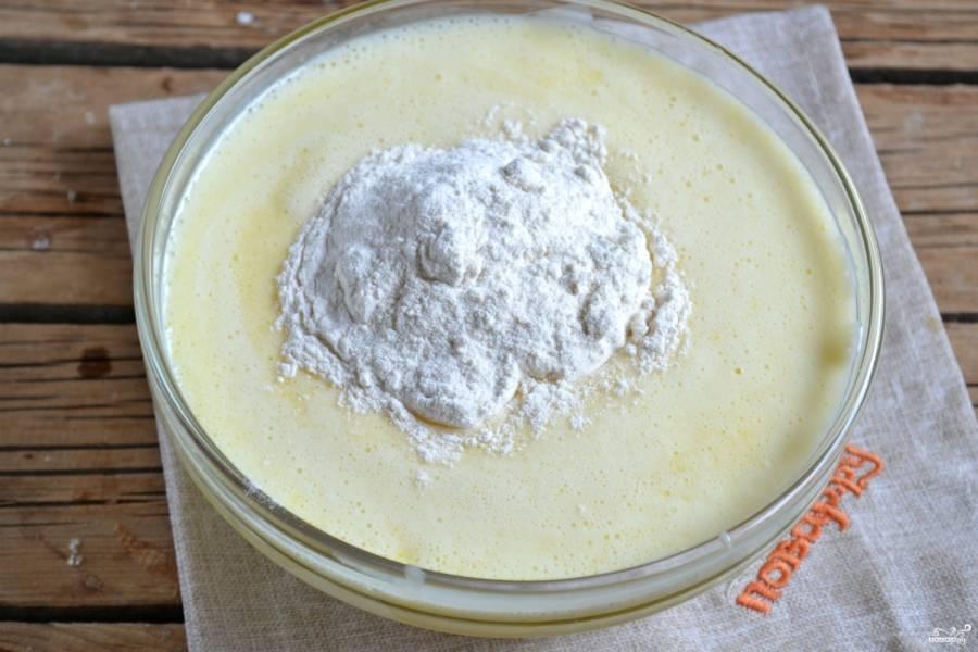 Добавьте муку, хорошо перемешайте ложкой тесто. Оно получится клейким и негустым.