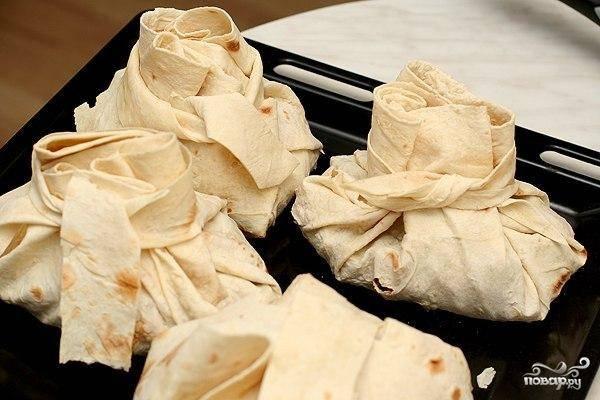 Завернутые и завязанные лаваши ставим в разогретую до 160 градусов духовку на 15-20 минут. Лаваш должен стать хрустящим. Готово - подавать к столу сразу же, пока не остыло.