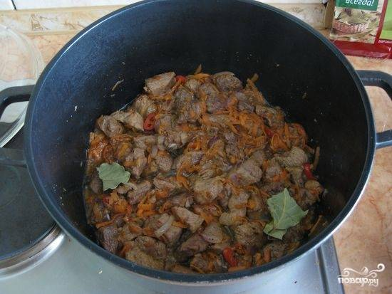 Лук и морковь нашинкуйте. Как только выпариться вода, добавьте их к мясу. Когда блюдо будет практически готово, закиньте лавровый лист, перец, специи и соль.