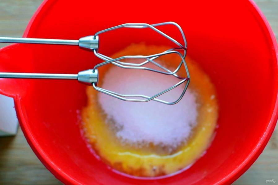 Начните приготовление с бисквита. Разделите яйца на белки и желтки. Желтки взбейте ср 100 г сахара добела, затем, подливая порциями теплую воду, взбейте до образования пышной пенной массы.