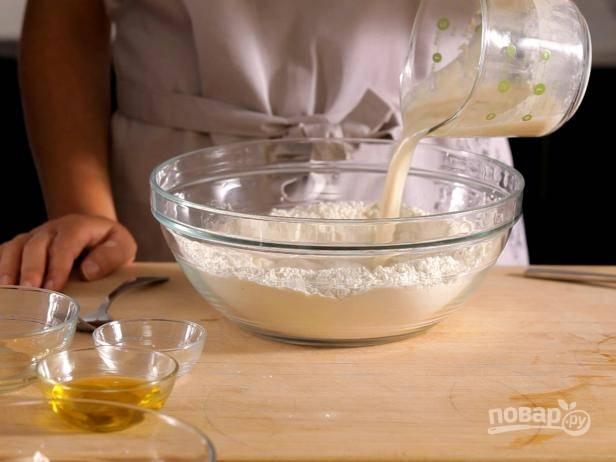 1. В глубокой емкости смешайте муку и соль. Активируйте дрожжи, смешайте их с сахаром и залейте теплой водой. Вылейте эту смесь и масло в муку и перемешайте.