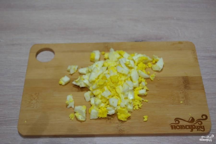 Куриные яйца нарезаем мелко. Добавляем в салатник.