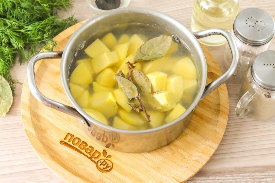 Залейте горячую воду, добавьте лавровые листья и отварите картофель примерно 8 минут.