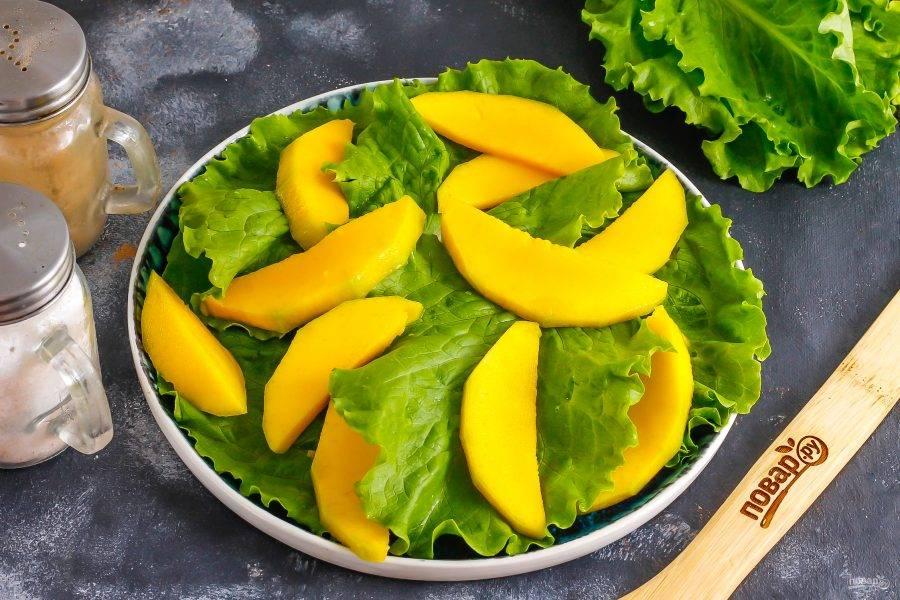 Манго очистите от кожуры, срежьте с косточки и нарежьте ломтиками. Выложите между листьями салата.