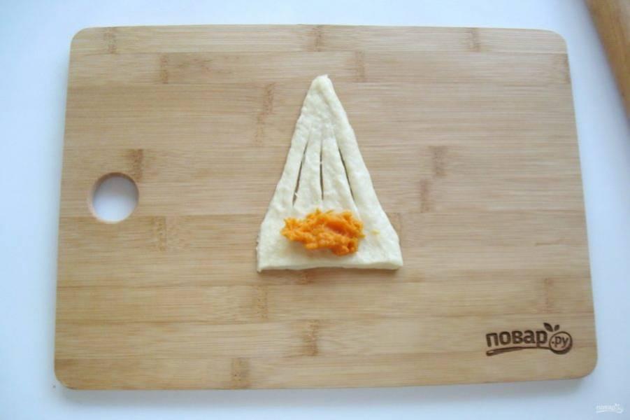 Тесто раскатайте и нарежьте треугольниками. Надрежьте их в трех местах, как показано на фото. Выложите на широкую сторону треугольника начинку.