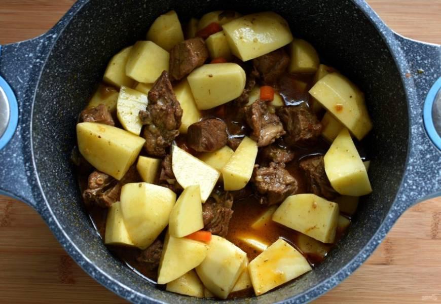Картофель нарежьте крупно и добавьте к мясу. Посолите и тушите на среднем огне. Регулируйте жидкость - ее должно быть немного ниже уровня продуктов.