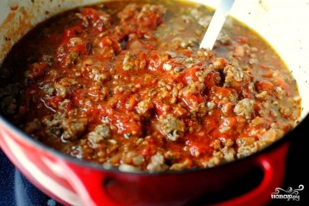 6. Следом выложите томатный соус или помидоры в собственном соку, предварительно размяв их вилкой или прямо руками. Уберите огонь до минимума, оставьте томиться минут на 35 под закрытой крышкой.