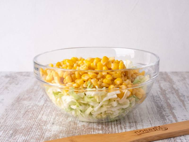 Капусту мелко порубите и немного помните руками с небольшим количеством соли. С кукурузы слейте рассол и добавьте к капусте.