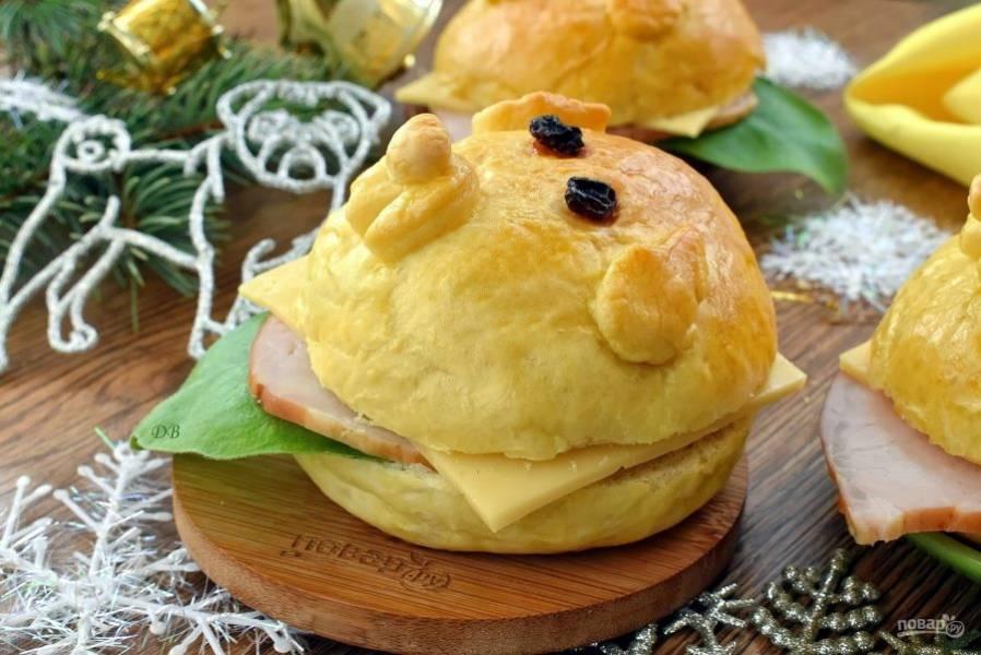 Разрежьте готовые булочки на две части, смажьте срезы смесью майонеза и горчицы, соберите гавбургер. На нижнюю часть положите лист салата, лук и огурец, нарезанные колечками, ломтики ветчины и сыра, накройте верхней половиной булочки. Приятного аппетита! С наступающим Новым годом!
